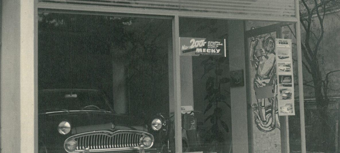 Schwarzweißfoto Fahrzeugverkaufsauslage mit altem Fahrzeug
