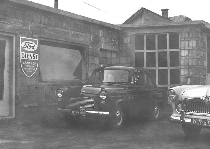Schwarzweißbild Ford Dienst Werkstatt mit Oldtimern im Vordergrund 1959