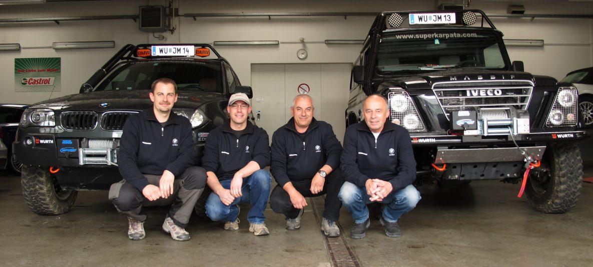 4 Männer vor zwei aufgerüsteten Geländefahrzeugen der Marken BMW und Iveco für die Gelände Challenge Super Karpata