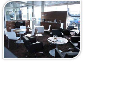 Kundenwartebereich mit braunem Teppich, gemütlichen Lederstühlen und Kaffevollautomat