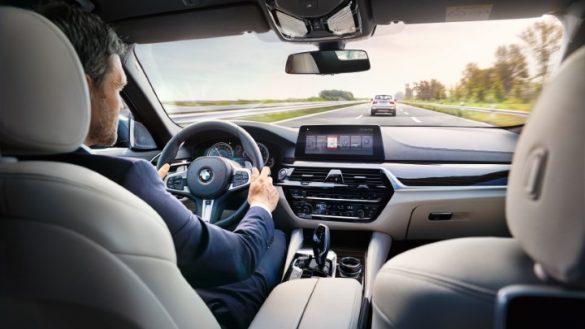 BMW Cockpit mit Mann im Anzug am Steuern und aktiviertem iDrive